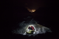 The lights of Longyearbyen are visible as researcher Stephen Jennings appears from at the entrance to this glacial cave system. Most of the team's work is done during winter months, during 24-hour arctic darkness. Credit: Ethan Welty.